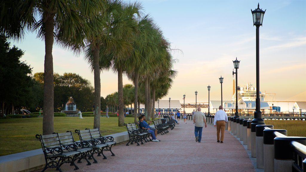 Charleston Waterfront Park showing a sunset and a park as well as a small group of people