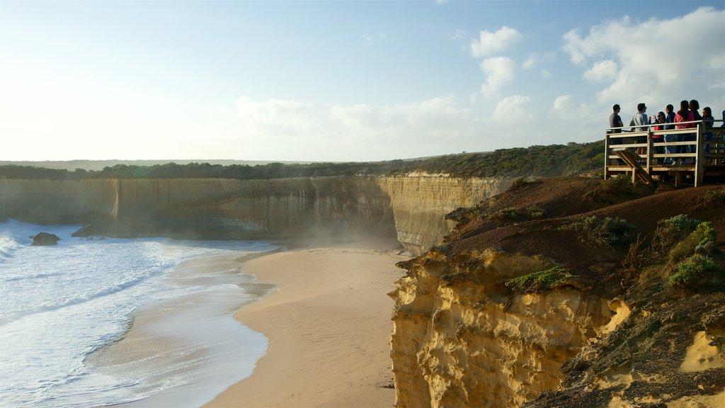 Port Campbell ofreciendo vistas y una playa de arena y también un gran grupo de personas