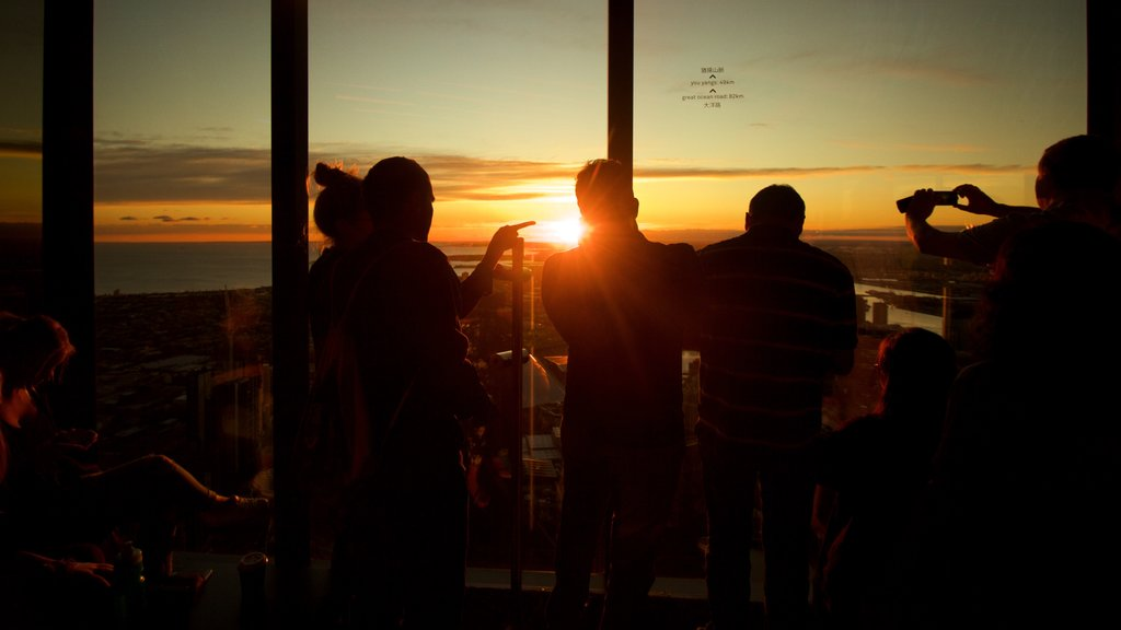 Eureka Tower showing a sunset and views as well as a small group of people