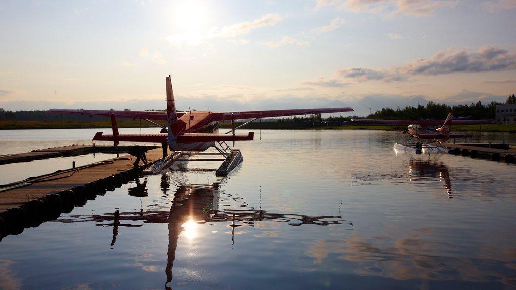 Kenai que incluye una puesta de sol, aeronave y una bahía o puerto