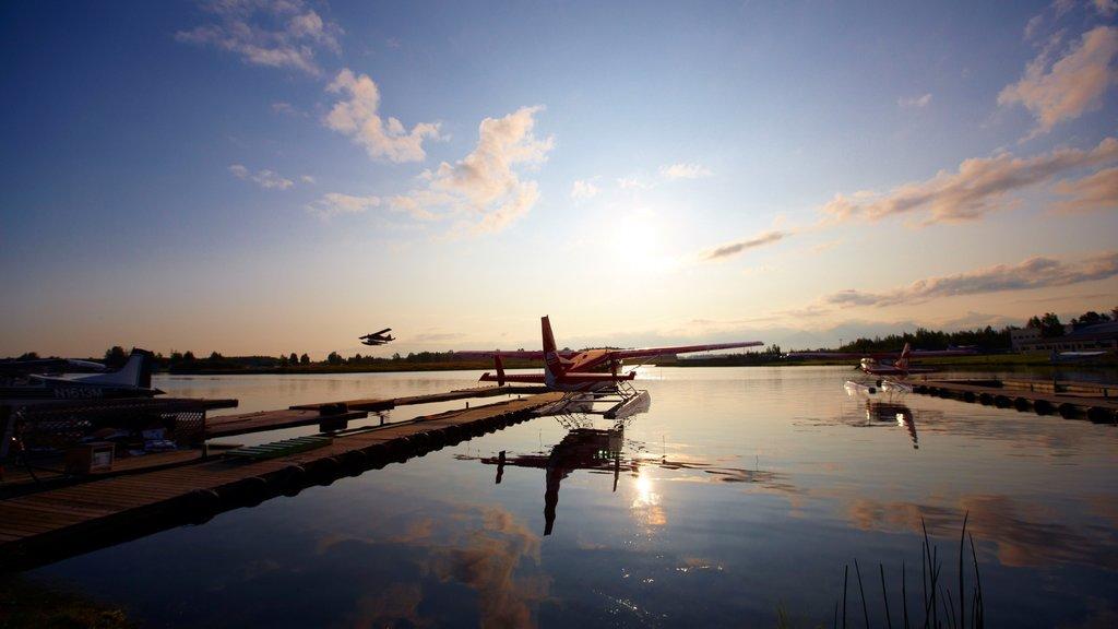 Kenai que incluye una puesta de sol, una bahía o puerto y aeronave
