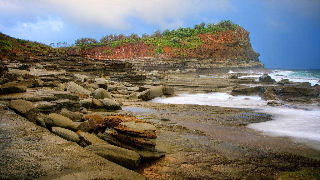 Terrigal which includes a bay or harbor, waves and rocky coastline