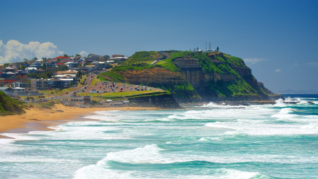 Newcastle which includes waves, a bay or harbor and a sandy beach