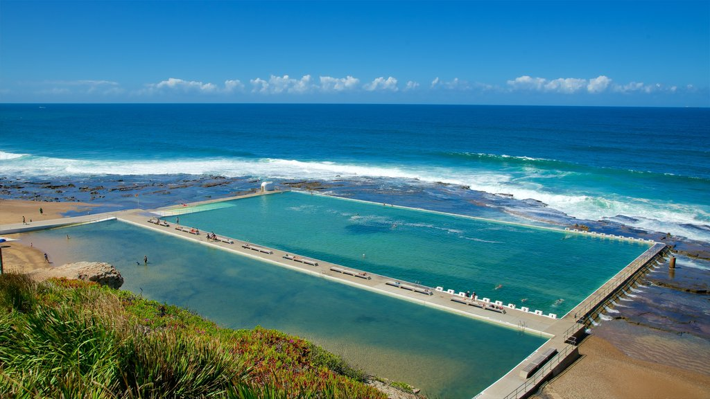 Newcastle showing a sandy beach, a bay or harbor and waves