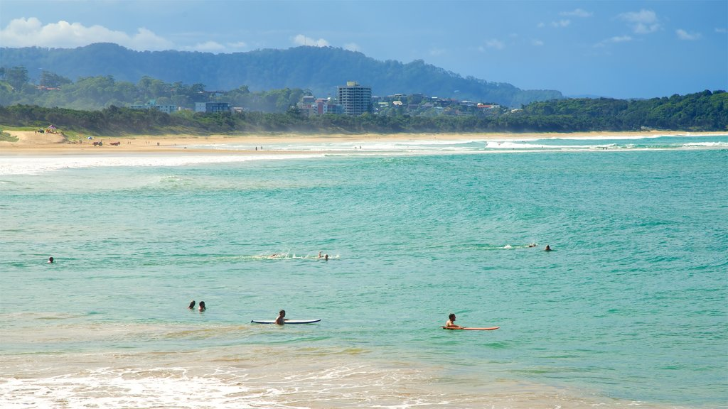 Coffs Harbour featuring swimming and a sandy beach as well as a large group of people