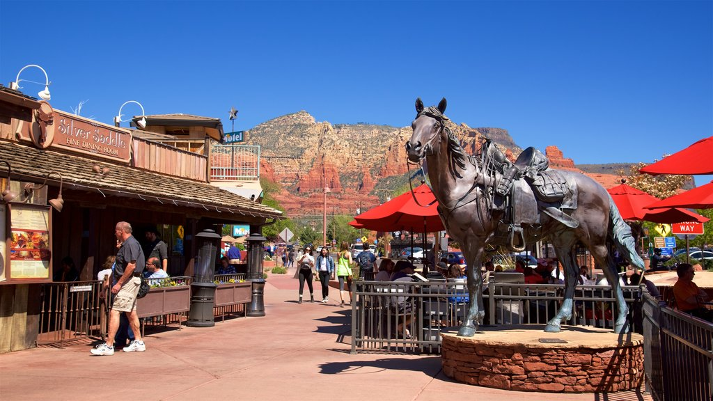 Sedona showing a statue or sculpture and cafe lifestyle as well as a small group of people