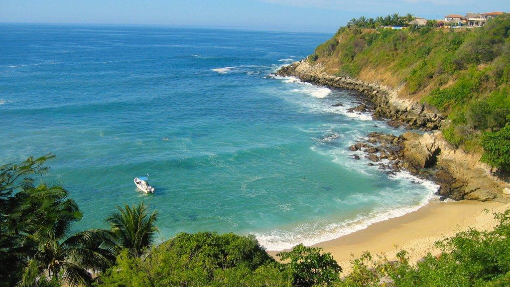 Oaxaca featuring a sandy beach, rugged coastline and a bay or harbor