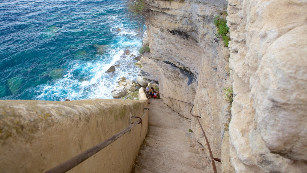 Escalier du Roi d\'Aragon which includes hiking or walking and rugged coastline as well as a family
