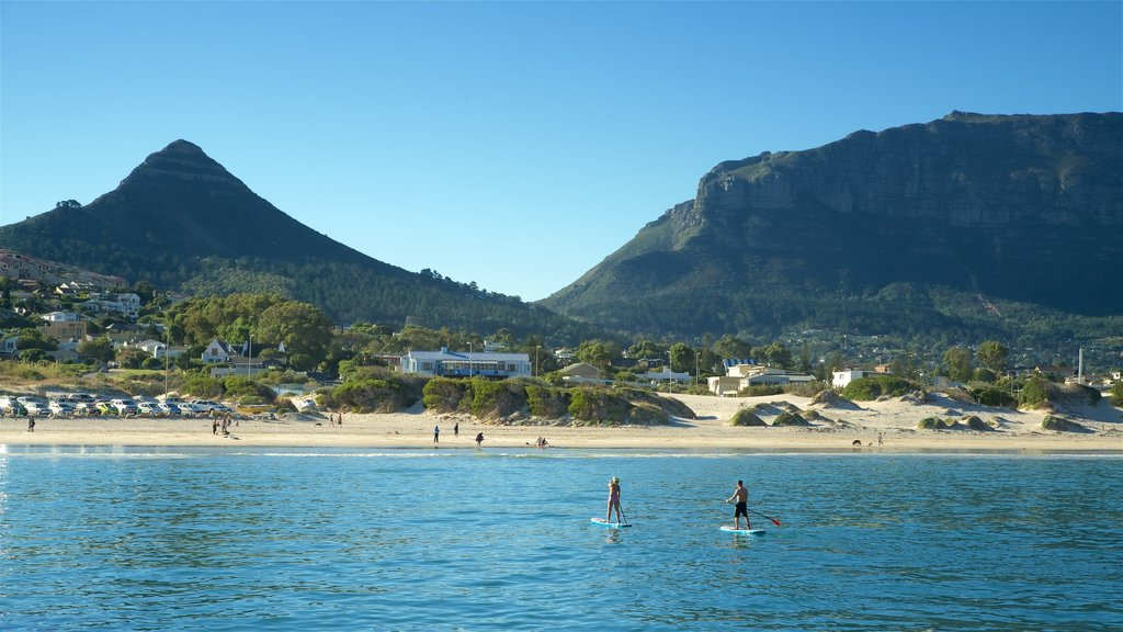 Hout Bay Beach featuring kayaking or canoeing and a sandy beach as well as a couple