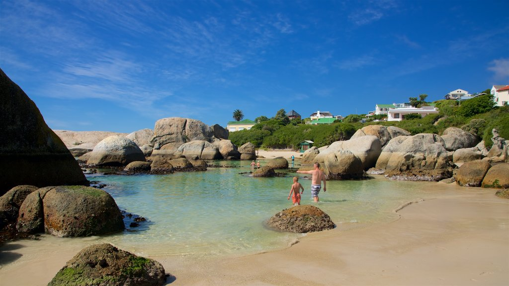 Boulders Beach showing rocky coastline and a sandy beach as well as a family