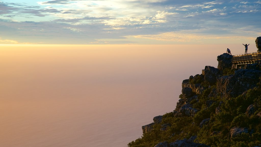 Table Mountain which includes a sunset and views as well as a small group of people