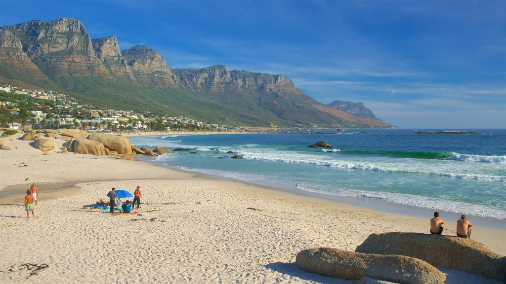 Camps Bay Beach showing a coastal town and a sandy beach as well as a small group of people