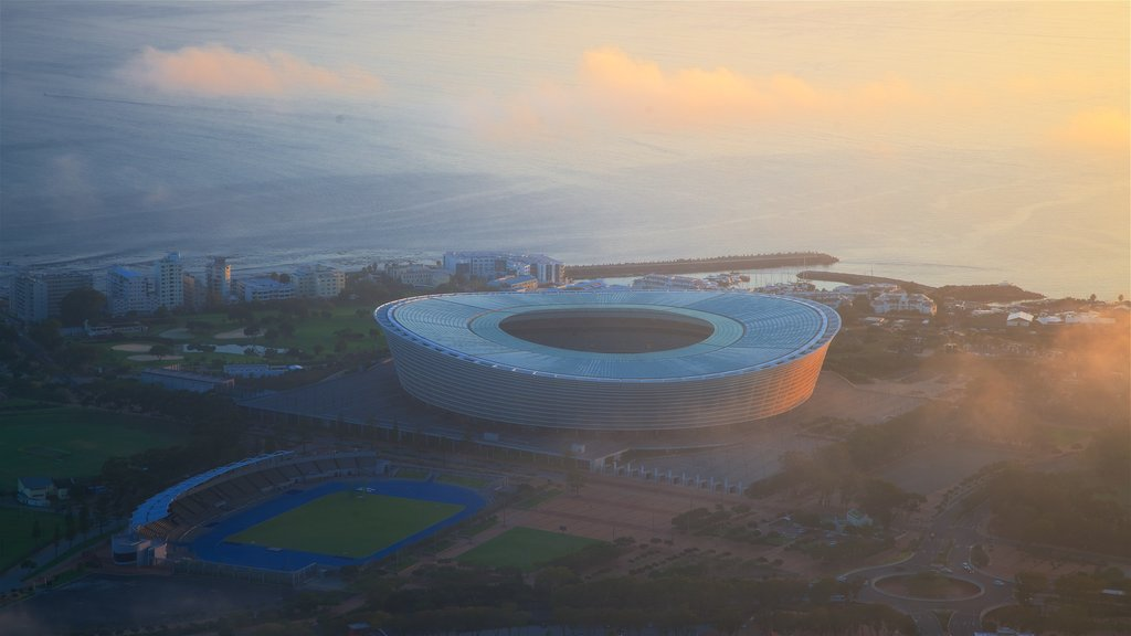 Cape Town Stadium featuring a sunset and a city