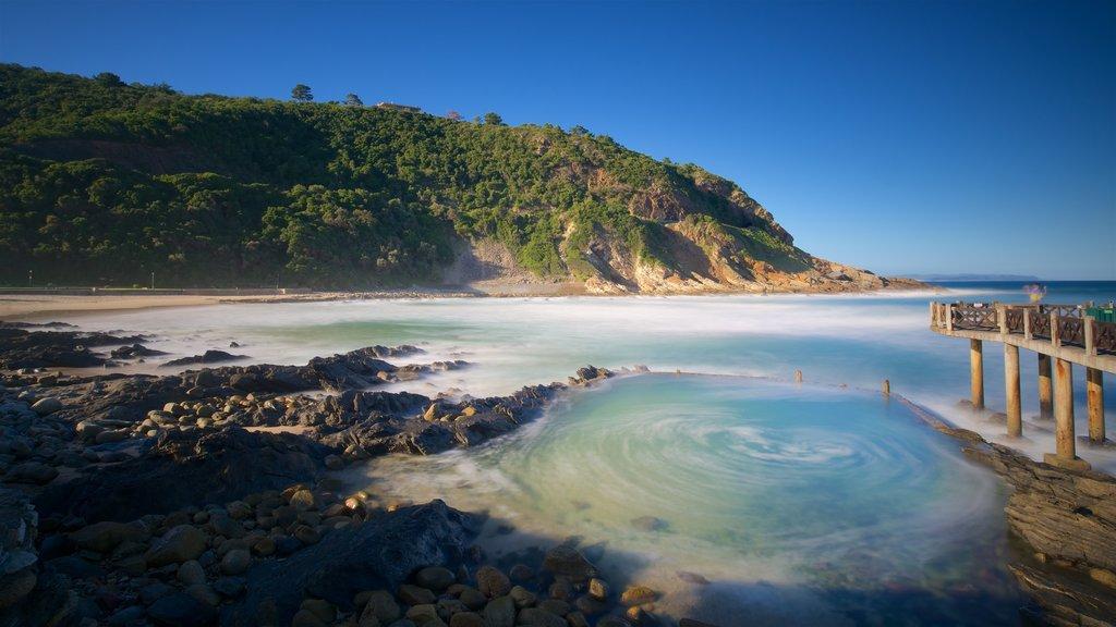 Victoria Bay Beach showing a sandy beach, a coastal town and rocky coastline