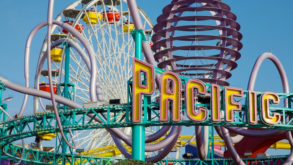 Santa Monica Pier showing signage, rides and a park