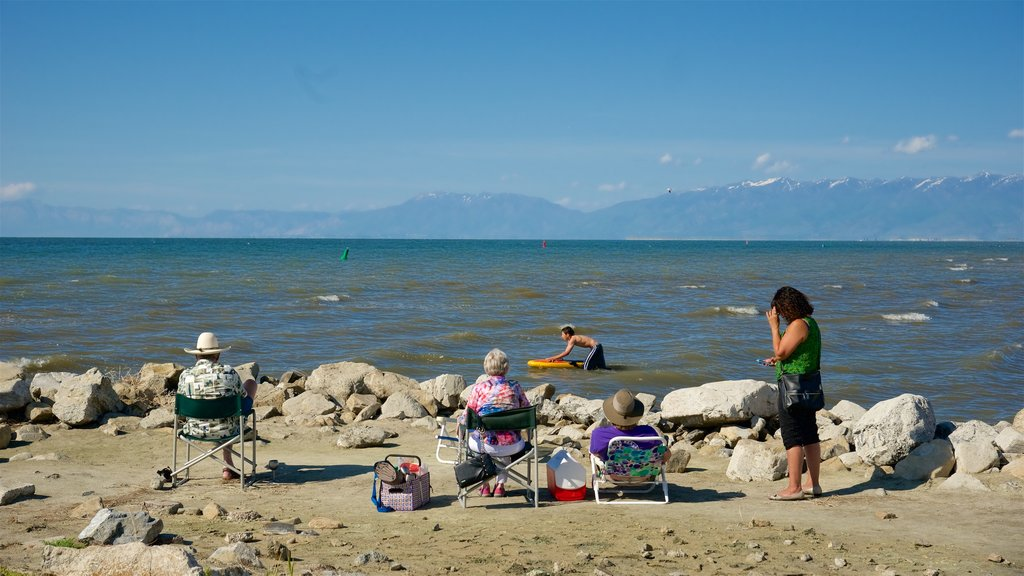 Great Salt Lake State Park showing a pebble beach as well as a small group of people