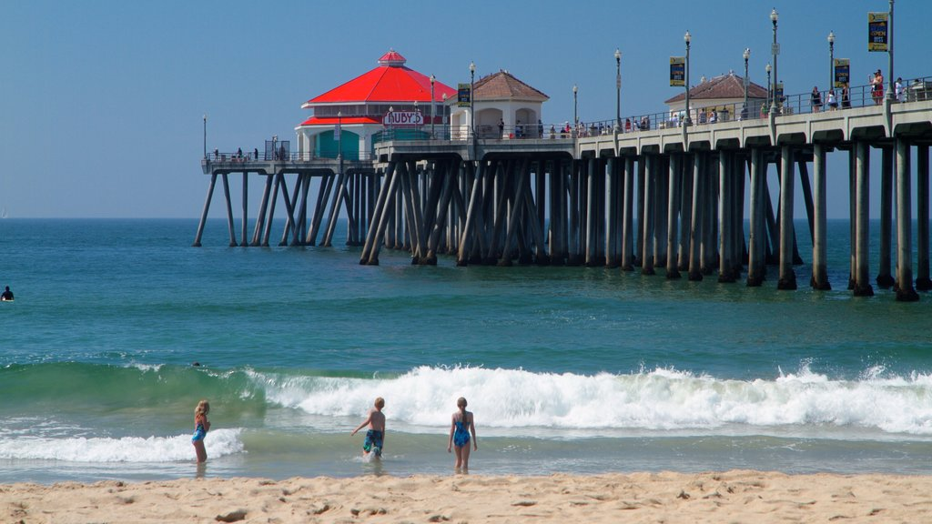 Huntington Beach showing landscape views and a beach as well as a small group of people