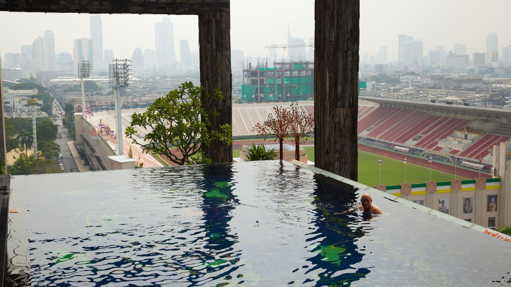 Bangkok featuring a pool and a city as well as an individual male