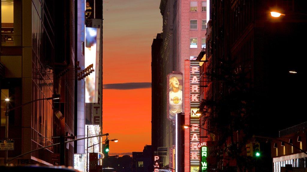 Times Square mostrando sinalização, uma cidade e um pôr do sol