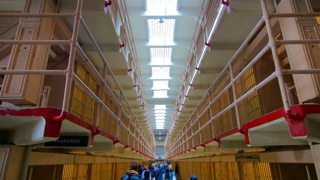 Alcatraz Island caracterizando vistas internas e elementos de patrimônio assim como um pequeno grupo de pessoas