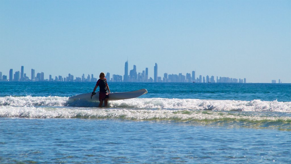 Coolangatta Beach showing surfing, general coastal views and a city