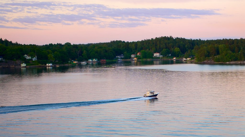 Estocolmo mostrando paseos en lancha, una puesta de sol y un lago o abrevadero