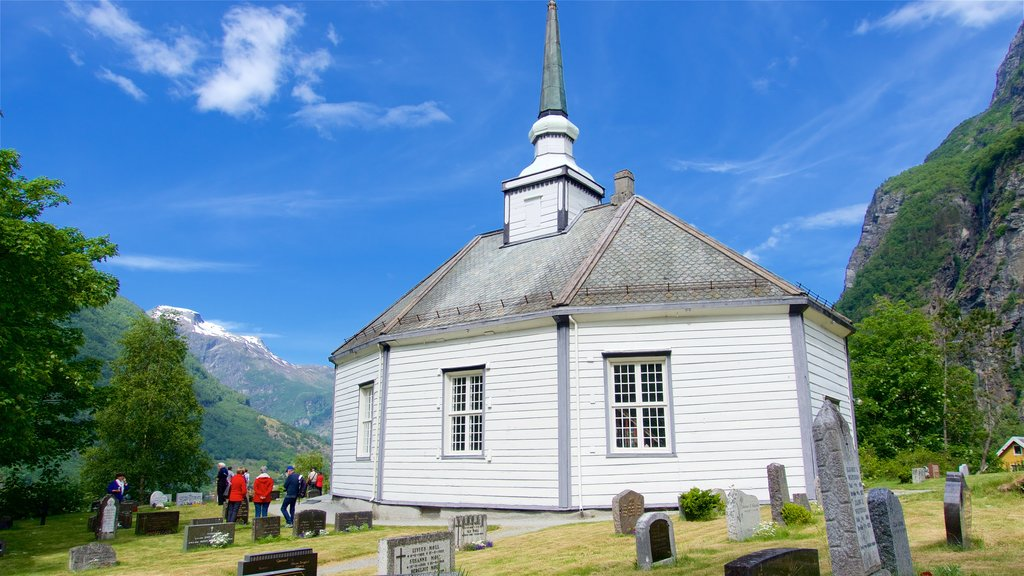 Geiranger featuring a cemetery and a church or cathedral as well as a small group of people