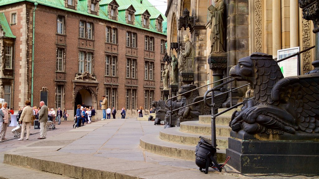 Bremen Cathedral featuring a statue or sculpture and heritage elements as well as a small group of people