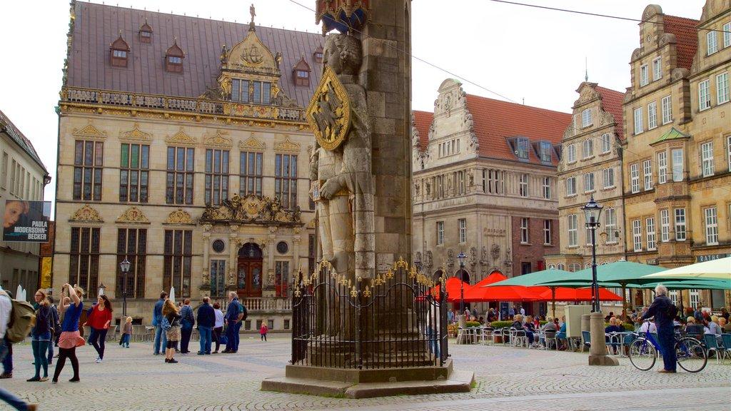 Estatua de Rolando de Bremen ofreciendo elementos del patrimonio y un parque o plaza y también un pequeño grupo de personas