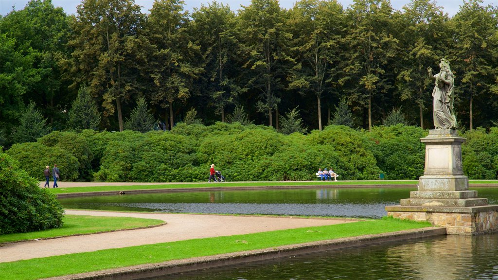 Bremen Buergerpark showing a park, a statue or sculpture and a lake or waterhole