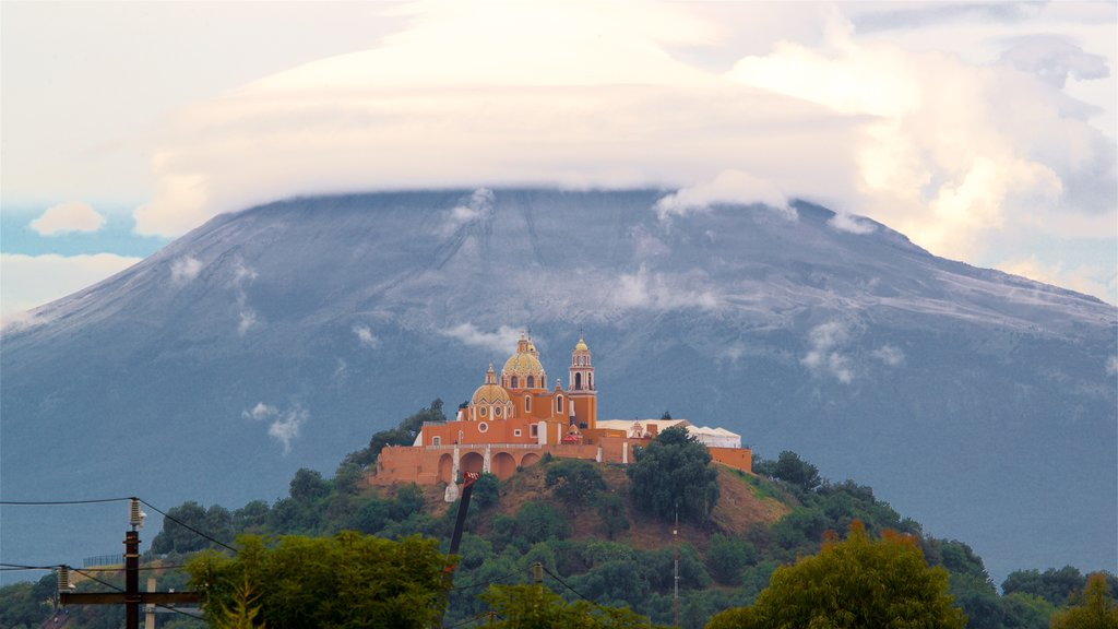 La Virgen de los Remedios Sanctuary featuring mountains, heritage elements and mist or fog