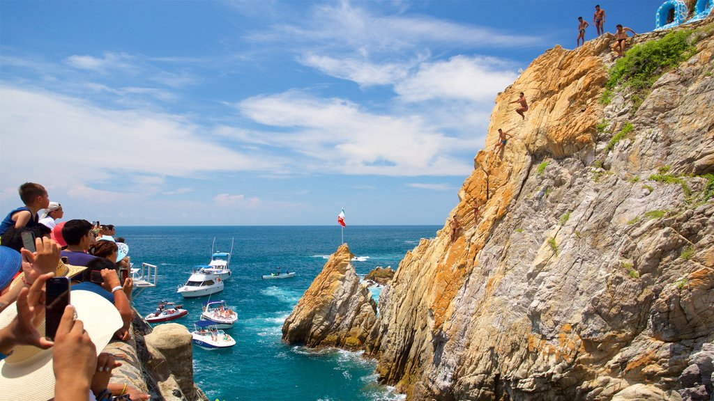 La Quebrada Cliffs which includes rocky coastline and a bay or harbor as well as a small group of people