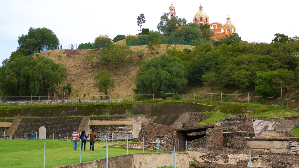 Great Pyramid of Cholula which includes heritage elements and building ruins as well as a small group of people