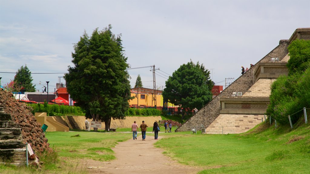 Great Pyramid of Cholula featuring heritage elements and a park as well as a small group of people