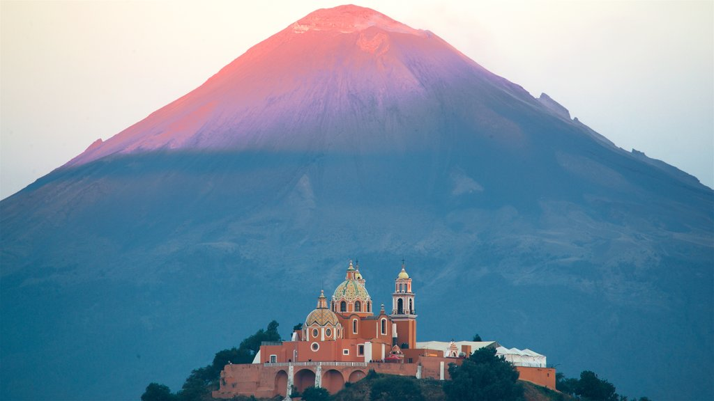 La Virgen de los Remedios Sanctuary showing mountains, heritage elements and a sunset