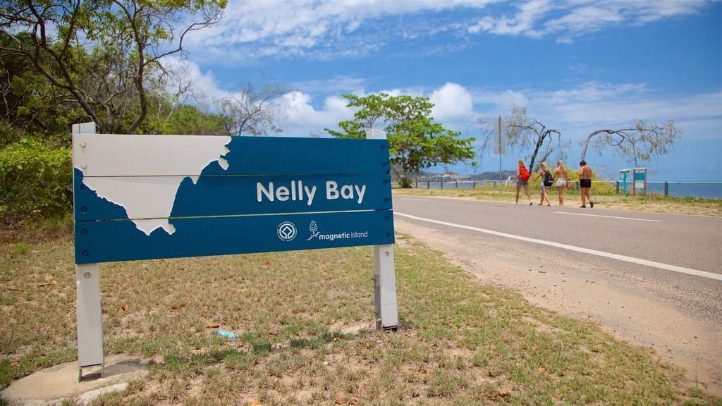 Nelly Bay which includes general coastal views and signage as well as a small group of people