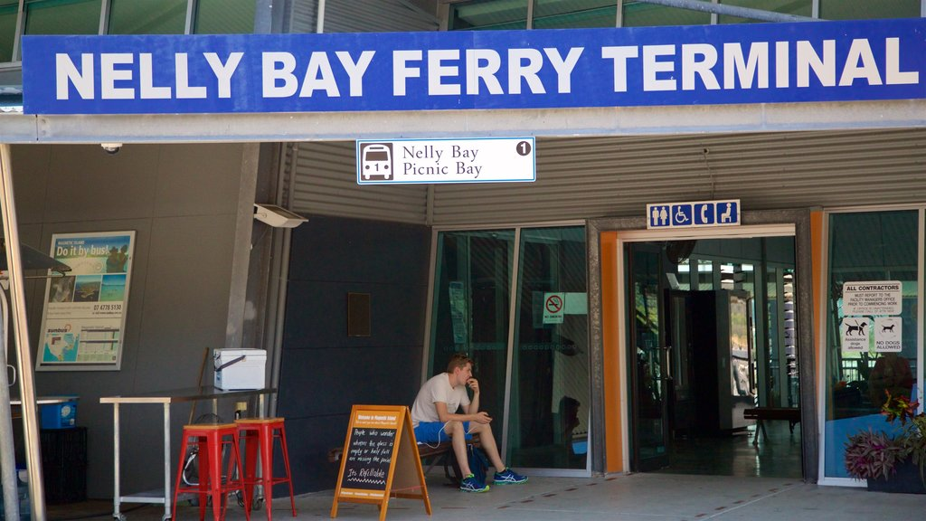 Magnetic Island Ferry Terminal showing signage as well as an individual male