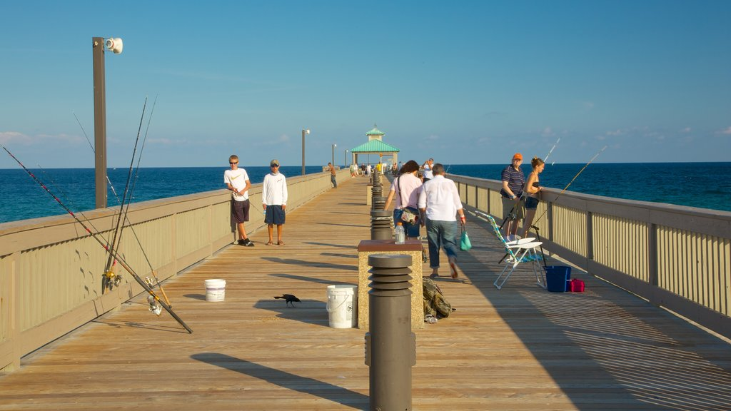 Deerfield Beach Pier showing fishing and general coastal views as well as a small group of people