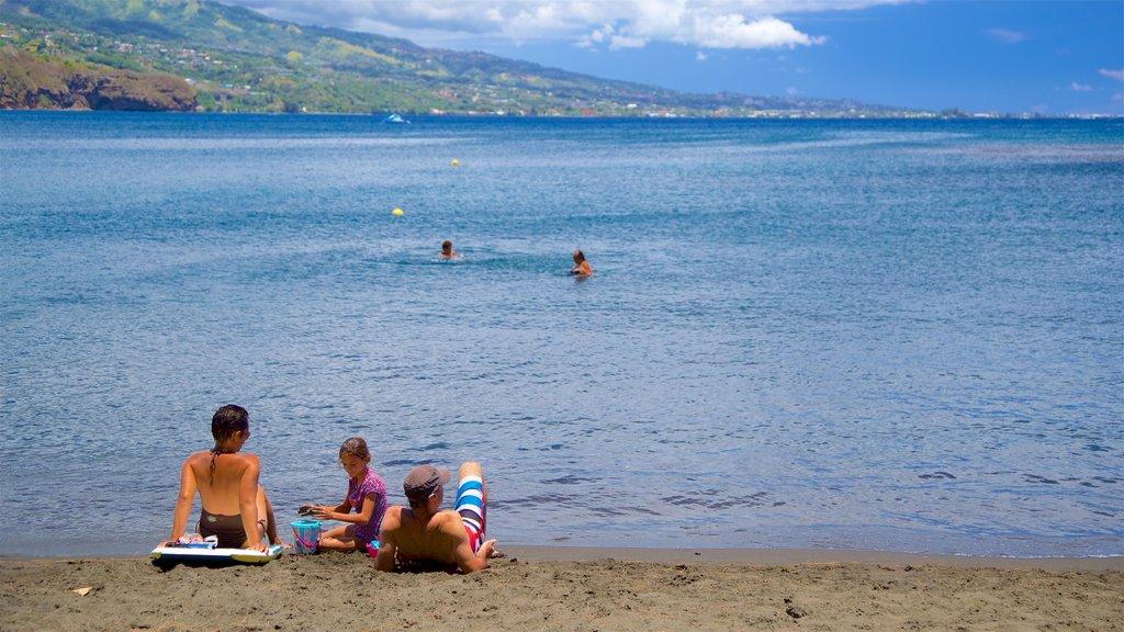 Playa de arena negra ofreciendo vistas generales de la costa y también una familia