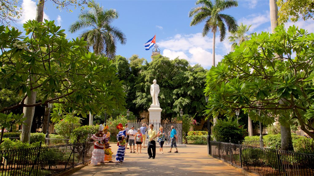 Plaza de Armas featuring a park and a statue or sculpture as well as a small group of people