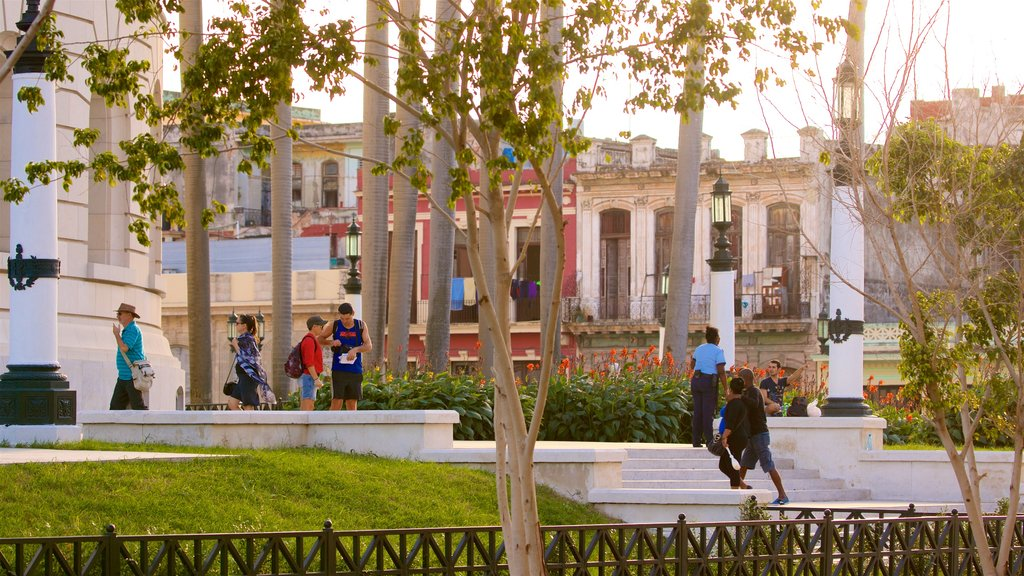 Capitolio Nacional showing a garden and a sunset as well as a small group of people
