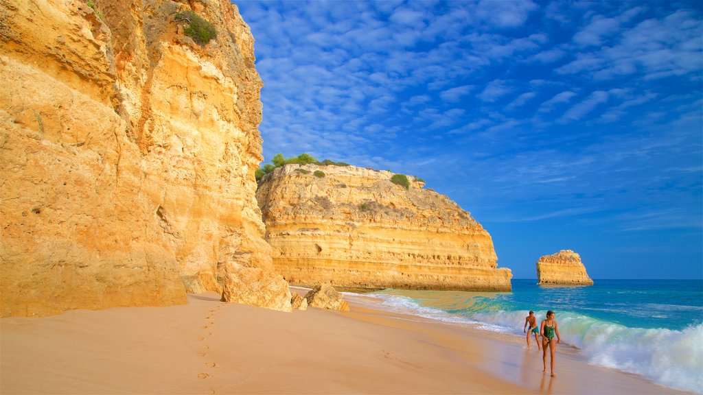 Marinha Beach featuring waves, a beach and rugged coastline