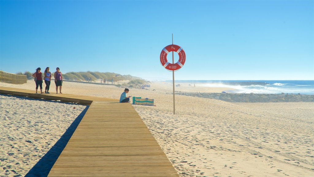 Praia da Costa Nova que inclui paisagens litorâneas e uma praia assim como um pequeno grupo de pessoas