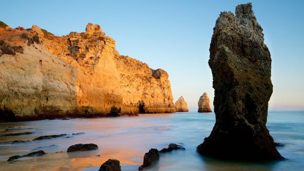 Playa Três Irmãos que incluye una puesta de sol, vistas generales de la costa y costa rocosa