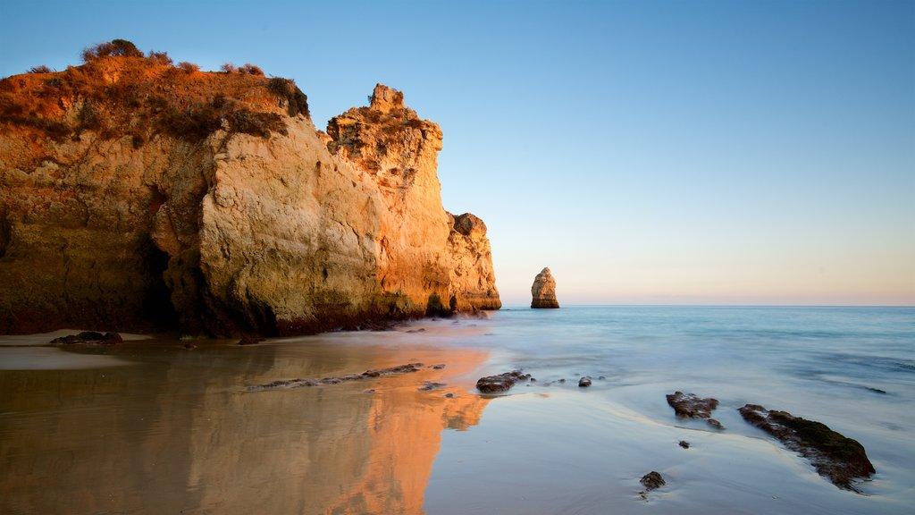 Playa Três Irmãos mostrando vistas generales de la costa, costa rocosa y una puesta de sol