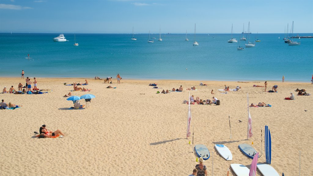 Cascais showing a sandy beach and general coastal views as well as a small group of people