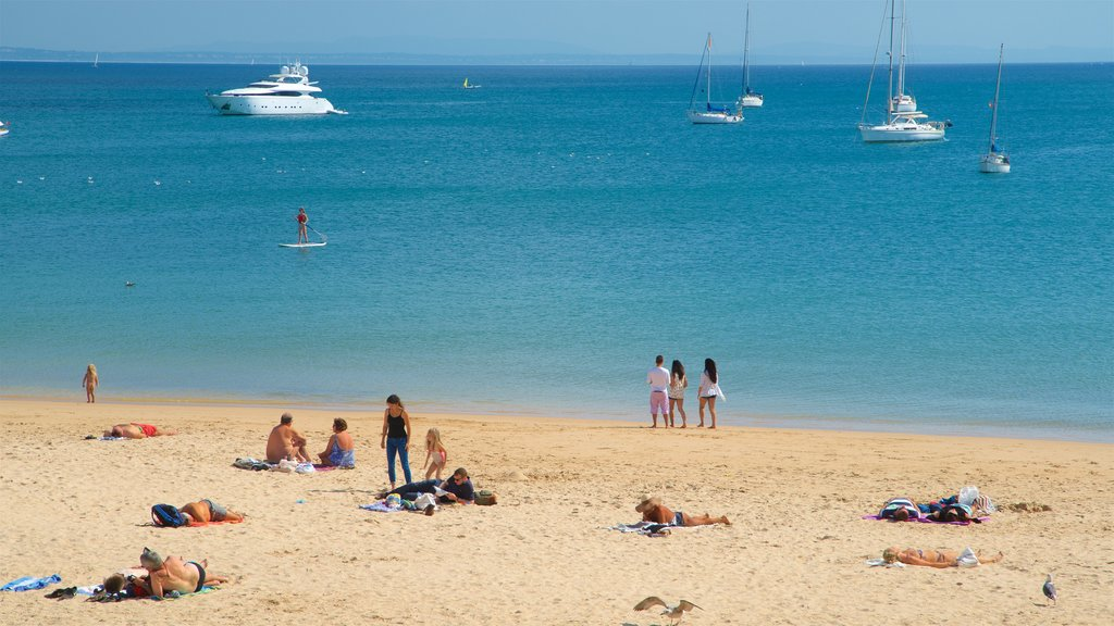 Cascais featuring a beach and general coastal views as well as a small group of people