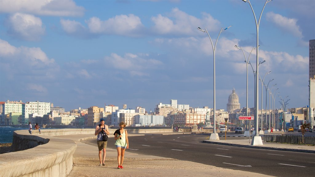 Malecon which includes a city as well as a couple