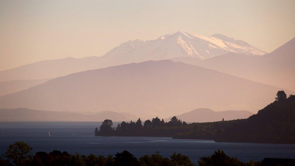 Lago Taupo mostrando montañas, una puesta de sol y un lago o abrevadero