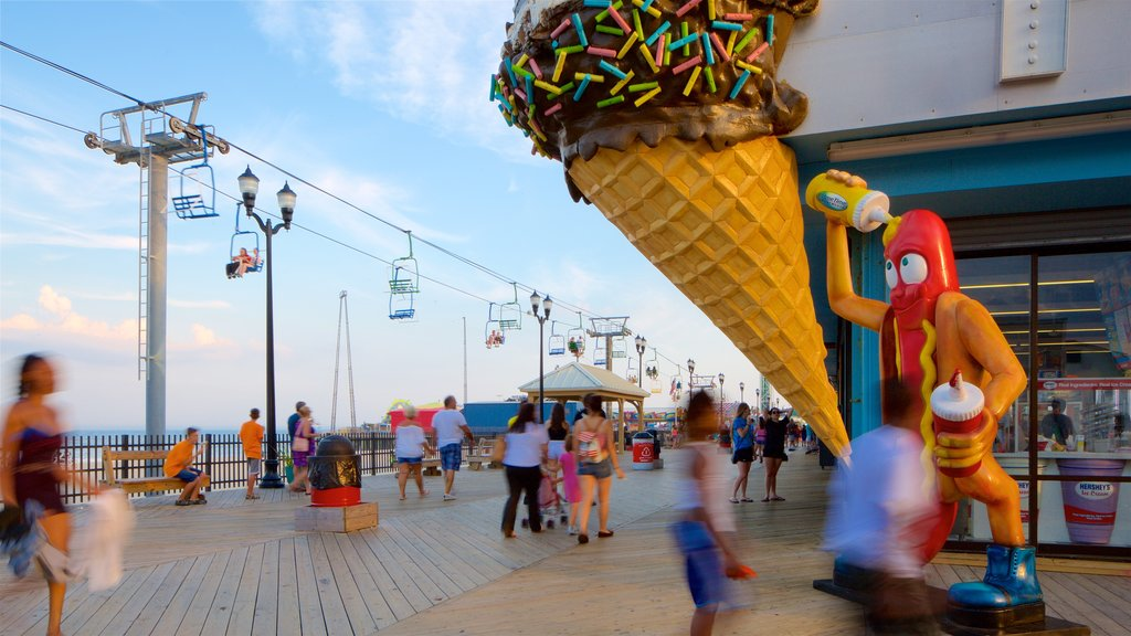 Seaside Heights showing signage and a gondola as well as a small group of people